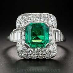 Emerald and Diamond Ring. Emerald and diamond rings rarely get more spectacular than this mid-century classic jewel. The vibrant Colombian emerald is framed with a diamond embellished platinum cushion featuring sparkling bead-set round diamonds, off-set with a channel of baguettes shimmering down the shoulders. The shank was replaced at some time in its long life with a more durable 10 karat shank