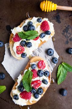 A spring breakfast. Generous smears of creamy ricotta cheese are paired with blueberries, raspberries, drizzled with lots of honey and tangy mint.