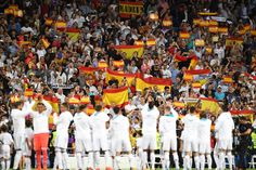 Real Madrid fans hoist Spanish flags above their heads in protest against Catalonia independence referendum after Barcelona play in front of empty Nou Camp (photos)