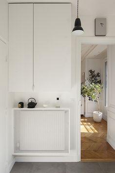 Nuovo classico a Parigi - Il pannello in acciaio forato nasconde il termosifone e il mobile su disegno è usato come piano d'appoggio. La cura del dettaglio ha permesso all'architetto di sfruttare tutti gli spazi a disposizione.