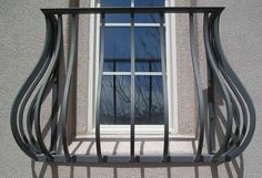 Shaped like a pot, this custom wrought iron window feature made by Holm Welding adds beauty and security to this window.