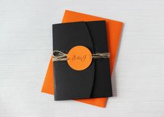 This elegant black pocketfold holds in a pop of orange, the main wedding invitation and two information cards. Held closed with a twine wrap and personalised monogram tag, the wedding invitation is a great mix of vintage style with a little touch of rustic introduced by the twine