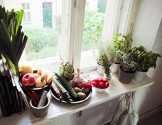 An extended window sill provides additional shelving for a cluster of potted herbs and farm-fresh goodies
