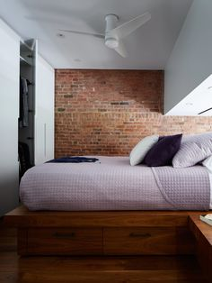 A variation on the system serves as a wardrobe in the sleeping loft. Additional storage can be found in the walnut platform with side tables. Although it appears less in the photo, the space between the platform and the lowest part of the ceiling is about four and a half feet, allowing René to comfortably sit up in bed. A Lutron screen lowers for privacy.