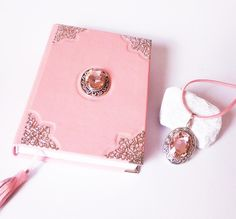 Pink #journal made from genuine #leather, with glass pearl pendant on antiqued silver base and a similar #pendant on a pink vegan suede leather necklace. A book to keep spells and secrets for girls and women Handmade Notebook, Notebook Ideas, Pendant Set, Pearl Pendant, Leather Gifts, Suede Leather, Leather Necklace, Leather Jewelry, Creative Notebooks