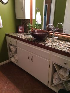 This my bathroom updating my old cabinets and existing mirror.  We made the countertop using tempered glass and river rock.