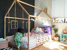 maisonnette en bois, lit bébé montessori, matelas, linge de lit, coussins multicolores, guirlandes, parquet clair, tapis noir à points blancs, rangement livres, mur d accent noir