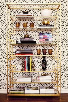 Fabulous gold bookshelf, and black and white wallpaper