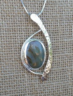 My u.niq designs include flowing features. This Sterling Silver Pendant is approx. 2-3/4 long and 1-1/4 wide. It has a 30 mm x 20 mm Pale Green Color Agate Cabachon as the focal point. Elegant flowing design that can be worn casually or more formal as desired.  I am including a Sterling Silver 18 inch long 1.3 mm 8 sided Snake Chain so it can be worn immediately.