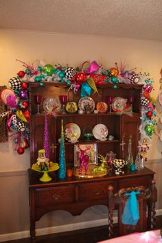 Christmas Garland Colorful Christmas Bright and beautiful ribbon, colorful ornaments and pops of black and white decorate this china cabinet. Grinch Christmas, Christmas Love, Christmas Colors, Winter Christmas, Christmas Themes, Christmas Crafts, Modern Christmas, Retro Christmas Decorations, Whimsical Christmas
