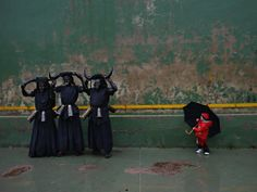 A boy looks at men dressed as 'Diablos de Luzon' (Luzon devils) prepare to join a traditional carnival in Spain