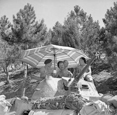 The crew of a Staghound armoured car of 1st King's Dragoon Guards shelter from the sun beneath a parasol fitted to the turret of their vehicle Italy 13 July 1944.