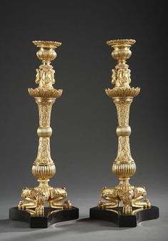 Pair of gilt bronze candlesticks on trilobed footed lion base adorned with palmettes and acanthus leaves and on a black marble curved sides pedestal. The stem finely chiseled with palm...