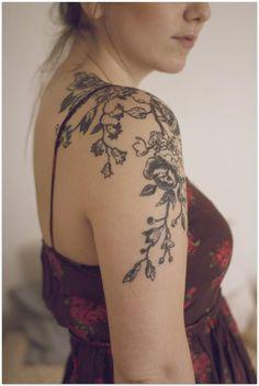 Photo d'un tatouage sur le bras et l'épaule d'une grande fresque florale.