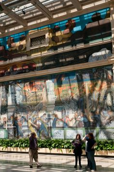 """A tour of the Detroit Institute of Arts begins in front of a slice of Diego Rivera's mural """"Detroit Industry"""", Detroit, Michigan."""