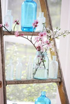 Colored glass and flowers on a ladder - a creative way to bring the colors of spring inside.