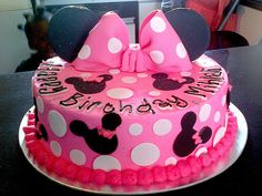 Wicked Chocolate cake iced in pink butter icing, decorated with pink puffy fondant bow with white polka dots, black Minnie Mouse heads, 3D black Minne Mouse ears, piped message by Charly's Bakery, via Flickr