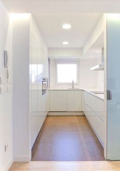 cuisine en U minimaliste blanche avec fenêtre et sol carrelé