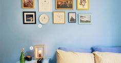 Parede azul e decorada com quadrinhos emoldurados