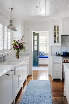 Restoration Hardware Harmon Pendant hanging over an apron sink next to a kitchen window suspended from a shiplap ceiling.