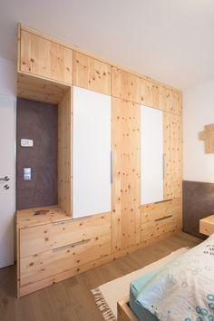 Deckenhoher Schrank aus Zirbenholz kombiniert mit weiß lackiert und Wandpaneel tapeziert mit Stoff. Der Schrank bietet besonders viel Stauraum.