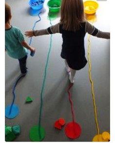 Träna balansen! När barnet kommit fram lägger den i ärtpåsen i hinken och balanserar tillbaka för att hämtar en ny