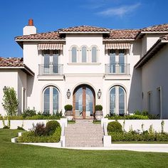 Reclaimed clay roof tiles and limestone-trimmed exterior windows and doors remain faithful to the home's European inspiration outside. Gas-powered lanterns, simple iron railings, and arched French doors imbue the exterior with old-world Tuscan flavor.