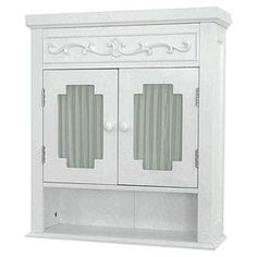 """2-door white wall cabinet with a bottom compartment and interior shelving.  Product: Wall cabinetConstruction Material: MDF and glassColor: WhiteFeatures:  Two glass window doors with white curtain One open shelf below Dimensions: 24.187"""" H x 21"""" W x 7"""" DNote: Assembly required"""