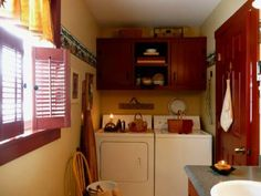 A Primitive Place ~ Primitive & Colonial Inspired Laundry Rooms; tan walls, red/burgundy cabinets, trim, shutters, black hardware