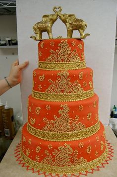 an Indian inspired wedding cake, with a vibrant colour palette of an Indian sunset, delicately piped with an intricate mehndi pattern and topped with two elephants- considered auspicious on an occasion like this.