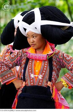 A woman from the Long Horn Miao tribe wears a ceremonial hairpiece, woven from her ancestors' hair, over wooden horns. The name of the tribe comes from the wooden horns worn by women to represent the strength of an ox. Guizhou Province, China