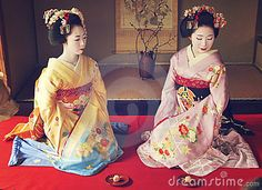 Real Geishas siting on their knees wearing the beautiful colors of the kimonos, unique atmosphere with a japanese background and the geiko's poses ! Geishas are girls skilled in traditional japanese arts. #Geisha #japan