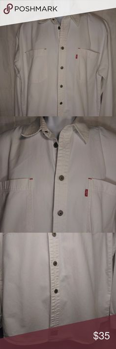 "Levi's Red Tab White Denim Button Front Shirt Levi's Red Tab Denim Button Front Shirt Size: Large Color: White Design: Button Front Neckline: Classic Sleeves: Long Sleeve Materials: 100% Cotton  Measurements (approximate) Length: 33.5"" Underarm to underarm (laying flat): 32""   Condition: Very lightly worn.  In excellent condition.  No stains, rips, or holes.  Two of the buttons have been replaced and don't match exactly, the top button and the very last button.  These can be seen in the…"