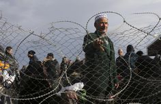 A Palestinian man, hoping to cross into Egypt, stands behind a fence as he waits at the Rafah crossing between Egypt and the southern Gaza Strip December 21, 2014. REUTERS/Ibraheem Abu Mustafa