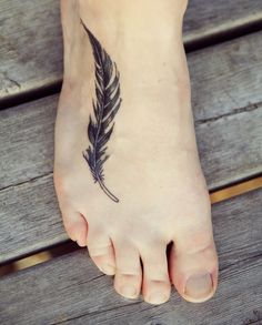 Traditional long black feather tattoo on foot