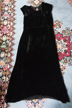 Lovely, simple 1930s black silk velvet gown with a cutout back. Small pleat at the neckline. Goes on over head, with one closure at the back of the neck. Dress is in good vintage condition. There are some seams exposed at the waist, its not noticeable. There is one repair under the arm.