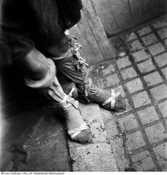Detail van de benen van een schaars geklede jongen voor een deur op straat in de hongerwinter, Amsterdam (1944-1945)