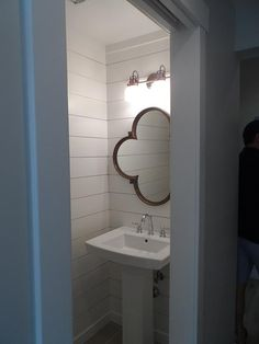 Small powder room features walls clad in shiplap lined with a wood quatrefoil mirror illuminated ...