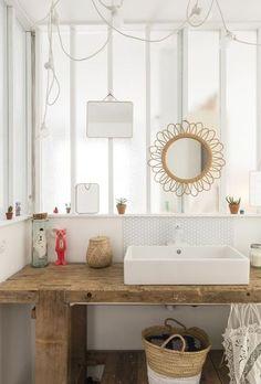 Le bois peut aussi être laissé brut dans la salle de bain pour un look plus rustique ou pour suivre la tendance Bohème, en vogue en ce moment ! Ce plan de vasque en chêne récupéré en brocante met en scène une vasque carrée posée contre une mini crédence en carreaux de verre.