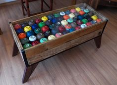 Mesa feita com madeira encontrada em caçamba de obra e sprays vazios.