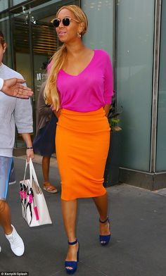 Stylish: Queen Bey showed off her shapely curves in a figure-hugging tangerine-hued skirt, which pleasingly clashed with a fuchsia V-neck top