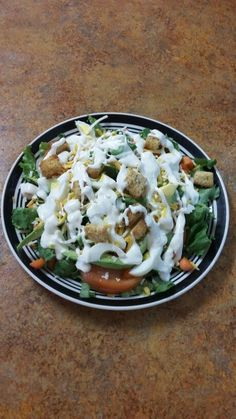 Salad with eggs  , tomatoes , cheese , crutons , carrots , onions , avocadoes , ranch dressing and celontro