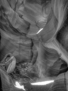 """Beams of sunlight shine down through a crevice of Lower Antelope Canyon, called Hazdistazi or """"spiral rock arches"""" near Page, AZ. It is a Navajo Sandstone formation caused by flash flooding during monsoon season."""
