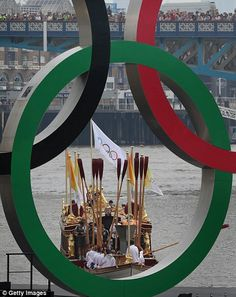 The end: The Gloriana arrives at Tower Bridge, left, where it is seen through the Olympic rings and right, Amber Charles is the final person to hold the torch