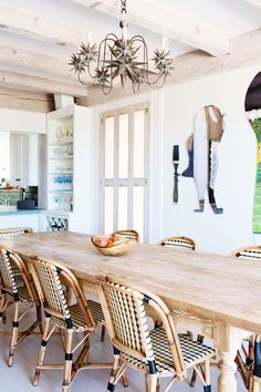 A Nickey Kehoe farm table surrounded by French rattan bistro chairs defines the dining room; artwork from artist Gracie DeVito hangs center stage on the wall | archdigest.com