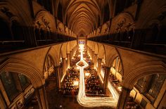 "the interior of Salisbury Cathedral is illuminated by trails of candles carried by choristers during the annual ""darkness to light"" advent procession in Salisbury, England. From Getty Images, The Atlantic"