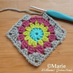 Unfinished granny square in the process of being done on the hook