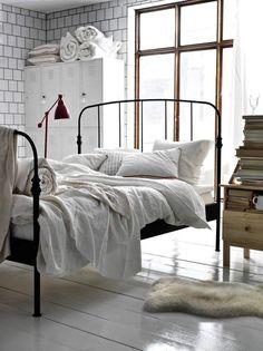 perfetto tutto: armadietto, muro, infissi, letto, coperte, lampada, pavimento, pelle di pecora
