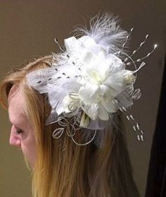 Fascinator with white flowers and feathers.