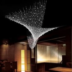 Celeste | Yellow Goat DesignThere is an elegant twist in this combination of long crystal strands. Each is built and weighted to create a deceptively simple helix and is lit by downlights in the ceiling above.
